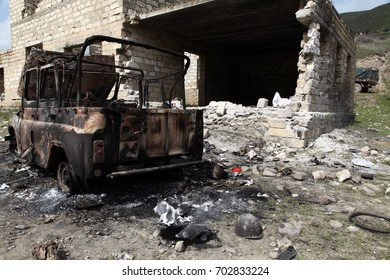 Destroyed car and building after bombing