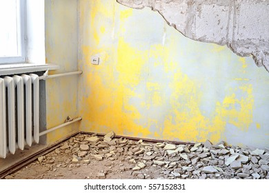 Destroyed dirty empty yellow interior with vintage radiator. Repair of apartments with old rusty cast iron central heating radiator or battery and old grungy cement wall with blank space for text
