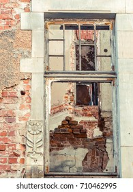 destroyed old brick house, Brick walls texture with broken windows. Damaged house in need of renovation.