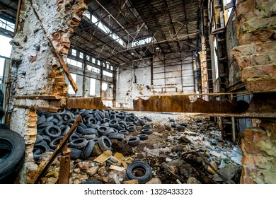 Destroyed old factory with garbage and a pile of used rubber tyres inside. Tires that are no longer suitable for use on vehicles in a damaged plant.