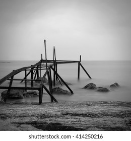 Destroyed pier. Black and white seascape.  Milk water. Photography with long exposure