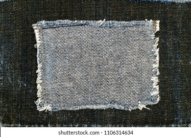 Destroyed torn denim blue - grey  jeans fabric frame on dark blue jeans background. Worn Jeans Casual Double Color patch Denim.