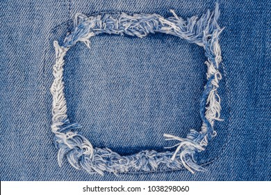 Destroyed torn ripped denim blue jeans patch. Ripped Destroyed Torn Denim Frame. Close up denim jean texture