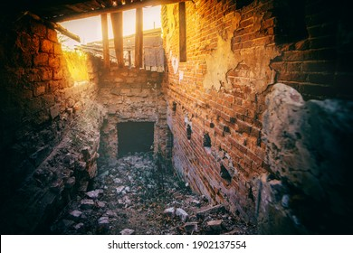 destroyed walls with openings and wooden structures through which sunlight breaks through in an old brick building, blurred image
