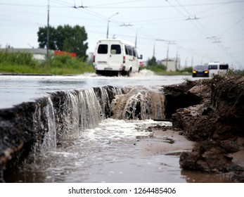 Destruction of the road after heavy rain. Water falls into a huge deep hole. Cars driving on a deep puddle