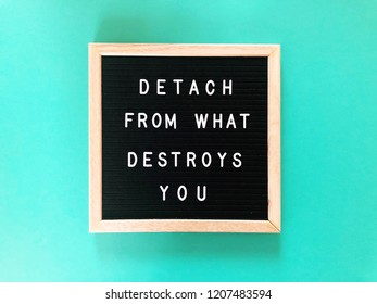 Detach from what destroys you. Positive message on black letter board. Turquoise green background.