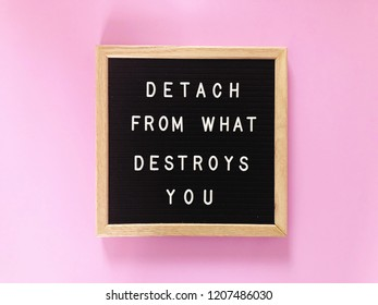 Detach from what destroys you. Positive message on black letter board. Pink background.