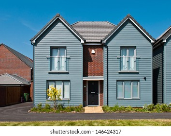 detached british residential house (beach style) with small entrance garden (blue sky)