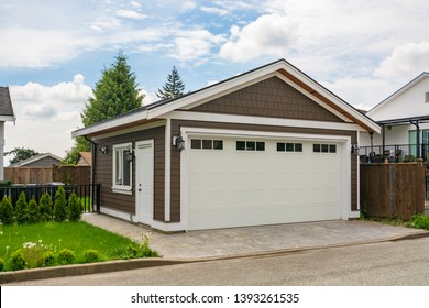 Detached garage of residential house with asphalt road in front