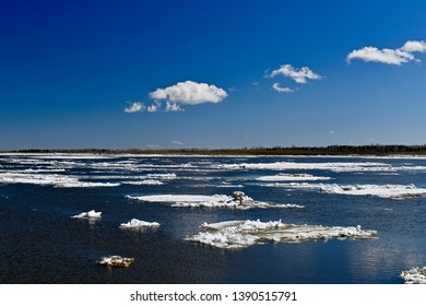 Detached ice floes float in blue water, in the spring along the river, like clouds above the sky.