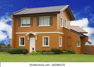 Detached single two story house with bright blue sky background.