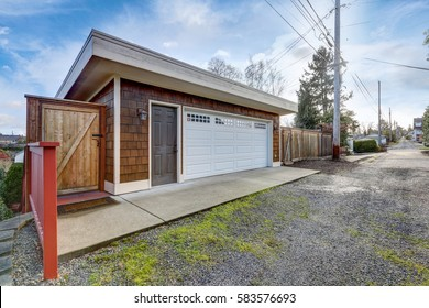 Detached two story garage with white folding door, blue sky background. Northwest, USA