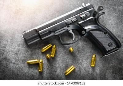 Detail of 9mm pistol, bullets and handcuffs. Gun with ammunition on dark stone background.