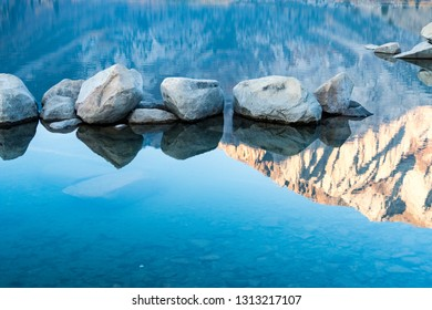 Detail abstract photo of rocks and the reflection of the Sierra Nevada mountains on a calm Convict Lake at sunrise in California