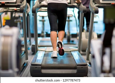 Detail of active woman walking on treadmill in health club gym