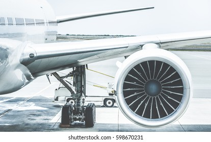 Detail of airplane engine wing at terminal gate before takeoff - Wanderlust travel concept around the world with air plane at international airport - Retro contrast filter with light blue color tones