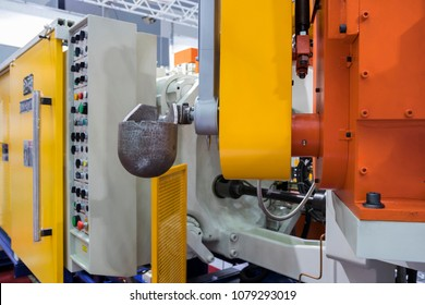 Detail of aluminum high pressure die casting machine ;focus at  ladle and robot arm ; industrial background