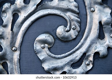 detail of a ancient metal door with spiral silver decoration