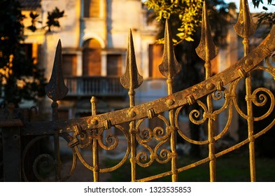 Detail of ancient rusty wrought iron gate with abandoned Venetian villa in the background
