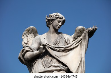A detail of the Angel with the sudarium, the cloth used to wipe the face of Christ, on the Ponte Sant'Angelo. The baroque statue can be seen against a deep blue summer sky.
