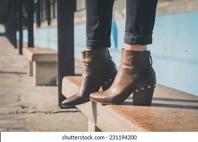 Detail of ankle boots on bench in a metro station