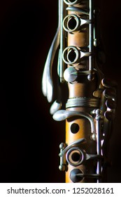 Detail of Antique clarinet on a black background.