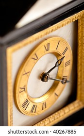 Detail of antique gold and black clock with Roman numeral, macro lens