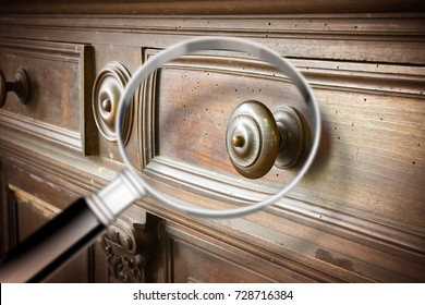 Detail of an antique wooden italian furniture just restored with a magnifying glass on foreground looking for woodworm threat detection