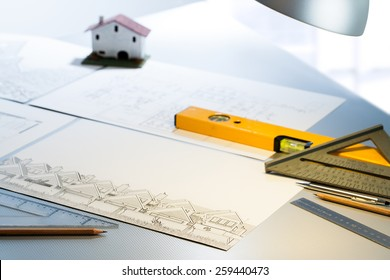 Detail of architect desk with technical drawings and measuring tools.