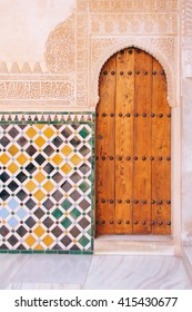 Detail of archway, wall tiles and decorative Islamic calligraphy on the walls of the Alhambra, Granada (Spain)