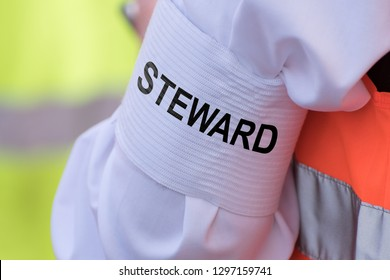 """Detail of an armband on the upper arm with the text """"STEWARD"""""""