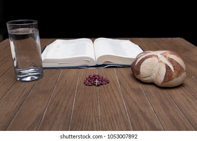 detail of artisan breads and water glasses on wooden table in dark room