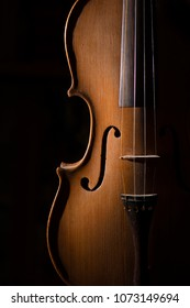 Detail of artisan violin on a black background.
