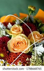 Detail of the artistic flower arrangement with three delicate roses. Closeup, copy space.