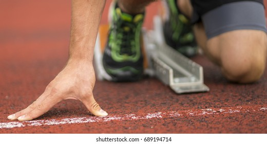 detail of an athlete in sprint start in track and field