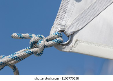 Detail of  awhit sail and knot in a rope of a recreation sailboat