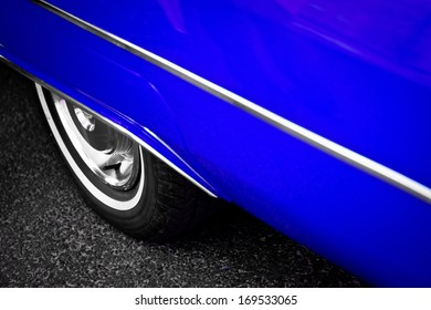 Detail of the back wheel of a vintage blue car