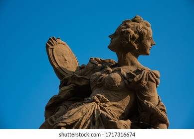 Detail of baroque statue with clear blue sky. Virtues and vices. Wisdom. Sunset light relecting on the limestone masterpieces.