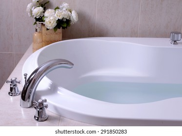 detail of bathroom, white bath tub with faucet and beige tiles, selective focus