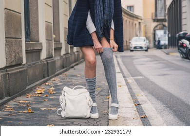 Detail of a beautiful girl with miniskirt posing in the city streets