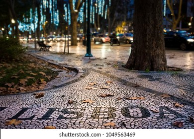 Detail of the beautiful Portuguese pavement at the Liberdade Avenue in the city of Lisbon, Portugal, with dry leaves; Concept for visit Lisbon in fall and welcome Lisbon