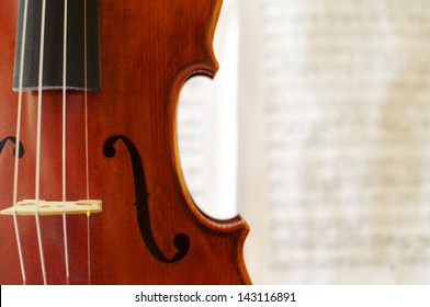 Detail of a beautiful violin with a blurred musical score in the background.