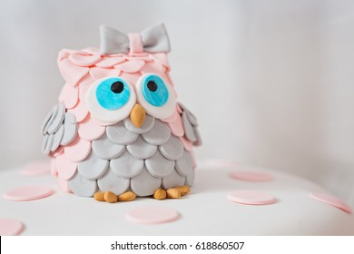 Detail of birthday cake covered with fondant displayed on the pink cloth and glass tray; decorated with pink dots and an grey and pink fondant owl with blue eyes sitting on top