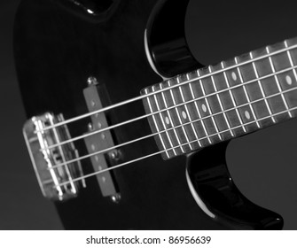 detail of a black bass guitar in dark back
