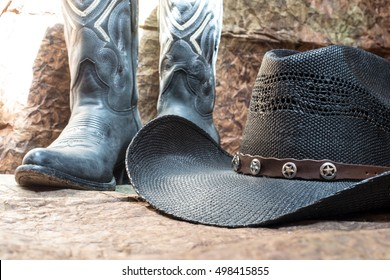 detail of black cowboy hat with blue boots