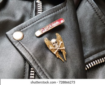 detail of black leather classic biker jacket with metal badges