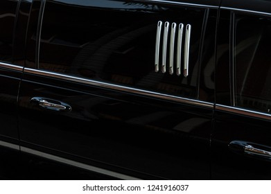 a detail of a black, shiny limo car