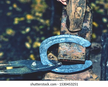 Detail to blacksmith arms forge horseshoe with hammer on anvil. Ancient craft. Village craft. Blacksmith working metallurgy