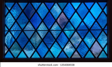 Detail of blue diamond shaped panes in colored light from stained glass window in catholic church