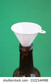 Detail of bottleneck with  white plastic funnel on a green background